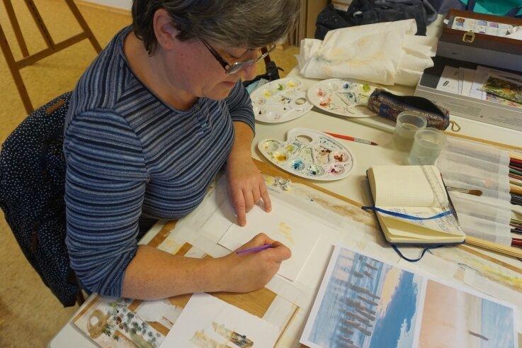 Konzentriert arbeitet Kathrin Werner an ihrem Aquarell. Das Thema sind Spiegelungen.