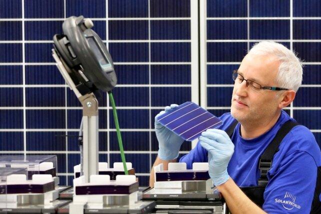 Ein Solarworld-Mitarbeiter der Modulfertigung prüft eine Solarzelle. Die Zellen werden in den Solarmodulen verbaut. Künftig soll die Produktion der Zellen in Arnstadt konzentriert werden.