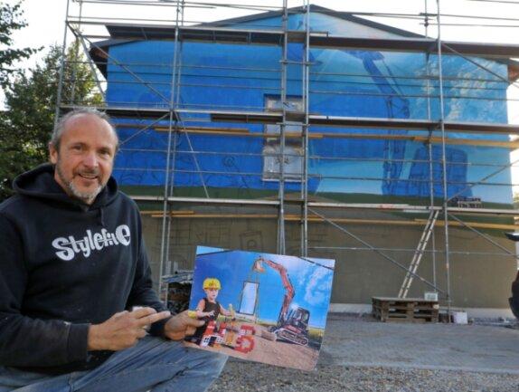 """Jens """"Tasso"""" Müller aus Meerane bringt das farbenfrohe Graffito an die Wand. Er hat auch am Entwurf des Fassadenbildes entscheidend mitgewirkt."""