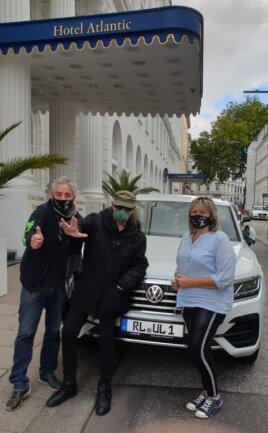 """Andreas Rosin, Udo Lindenberg und Irene Rosin (v. l.) feiern das markante Nummernschild """"RL UL 1"""" zu Ehren des Panik-Präsidenten vor dem Hamburger Hotel """"Atlantic""""."""