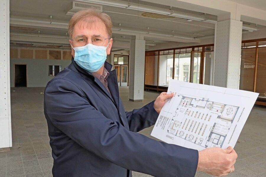 Crimmitschaus Oberbürgermeister André Raphael mit dem aktuellen Plan der künftigen Stadtbibliothek im ehemaligen Kaufhaus Schocken.