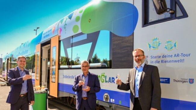 Michael Barth, der Geschäftsführer des Verkehrsverbunds Vogtland, Landrat Rolf Keil (CDU) und Länderbahn-Chef Wolfgang Pollety (von links) stoßen auf die Beklebung des Regio-Shuttles an.