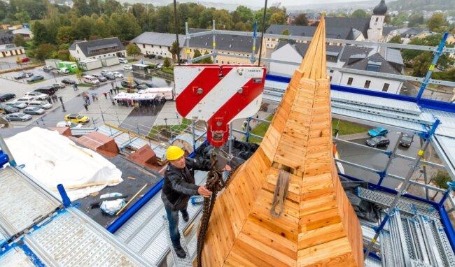 Am Haken eines Kranes schwebte die hölzerne Turmkonstruktion, musikalisch untermalt vom Steigerlied, auf das Dach des ehemaligen Postamtes, auf dem sie von Zimmerleuten montiert wurde.