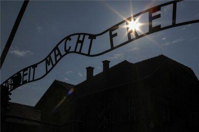 """Das Tor mit dem zynischen Schriftzug """"Arbeit macht frei"""" im früheren Stammlager des Konzentrationslagers Auschwitz. Dort, im nahe gelegenen Vernichtungslager Auschwitz-Birkenau und im Zwangsarbeitslager Monowitz, wurden bis Anfang 1945 etwa 1,1 Millionen Menschen ermordet."""