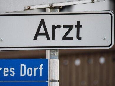 Ein Hinweisschild mit der Aufschrift «Arzt» ist in einem kleinen Ort angebracht.