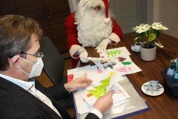 Weihnachtsmann und Stadtchef schauen die Bilder der Mittweidaer Kinder an.