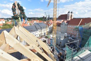 Architekt Christoph Frenzel sowie Bauingenieur und Zimmermannmeister Ralf Dechant aus Braunichswalde sehen zu, wie OB Sven Krüger den symbolischen letzten Nagel ins Dachgebälk einschlägt.