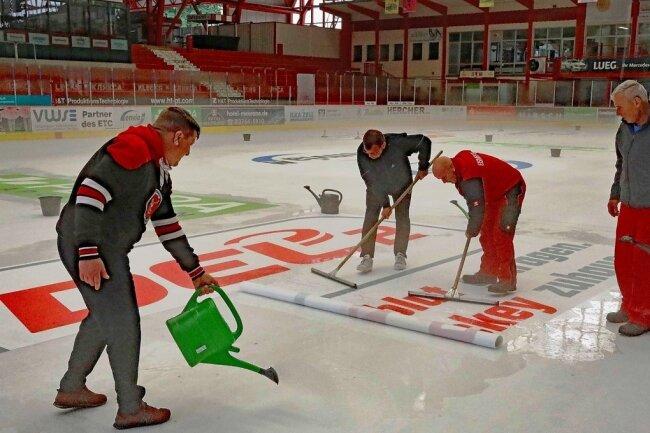 Daniel Katzke und Stefan Steinbock von den Eispiraten sowie die beiden Eismeister Jens Scholz und Stefan Wolf (von links) haben am Mittwoch die Werbung auf die Eisfläche aufgebracht - erstmals wurden hierfür Folien eingesetzt.