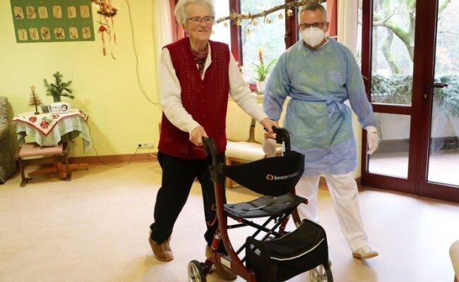"""Auch im """"Haus Jahreszeiten"""" gibt es Unterstützung von Bundeswehrangehörigen. Oberstabsgefreiter André Tretbar geht mit Ursula Körnig (85), die das Virus schon im März überstanden hat, auf dem Gang spazieren."""