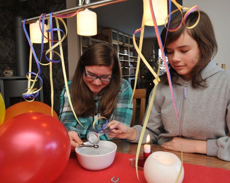 Austauschschülerin Bretta Doherty aus den USA probiert mit Gastschwester Nika Möller aus Burkhardtsdorf Bleigießen.