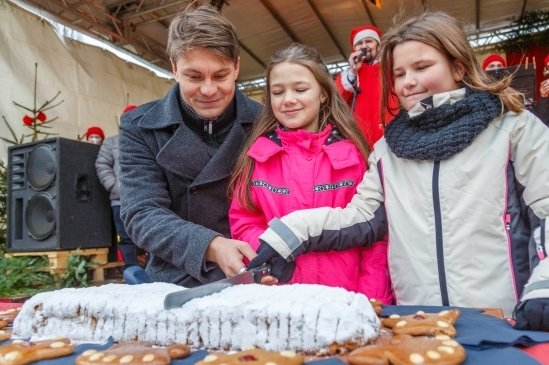 Auf dem Weihnachtsmarkt: Thalheims BürgermeisterNico Dittmann schneidet mit den Kinderbürgermeisterinnen den Stollen an.