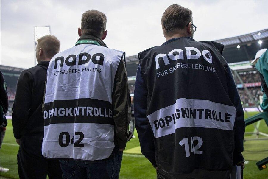 Alltag im Profifußball: Dopingkontrolleure warten nach dem Abpfiff am Spielfeldrand auf die zur Kontrolle ausgelosten Spieler.
