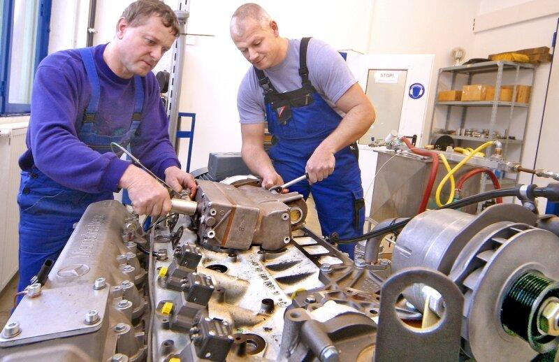 """<p class=""""artikelinhalt"""">Die Versuchsschlosser Frieder Schubert und Nico Richter (v. l.) arbeiten an einem Luftkompressor, der für große Nutzfahrzeuge und Busse entwickelt wurde.Ralph Hergödt</p>"""