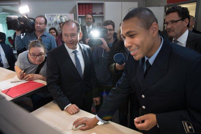 Sachsens Innenminister Markus Ulbig (CDU; links) lässt sich vom Leiter der Regionalleitstelle in Hoyerswerda, Stefan Schumann (rechts) vorführen, wie das neue Warnsystem funktioniert