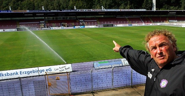 Stadion-Chef Volker Decker zeigt auf die beschädigte Spielfläche im Auer Erzgebirgsstadion, die seit Freitagmittag reichlich bewässert wird, um die von Unbekannten verteilte chemische Substanz zu neutralisieren.