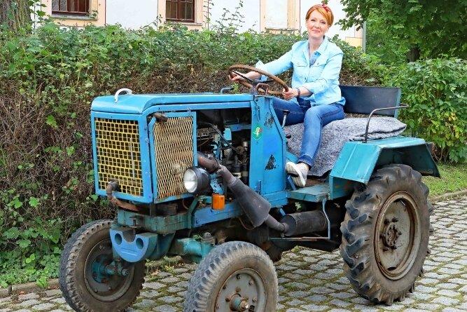 Moderatorin Beate Werner steuert den Traktor sicher vom Sportplatz über die Lindenallee in den Hof von Schloss Blankenhain.