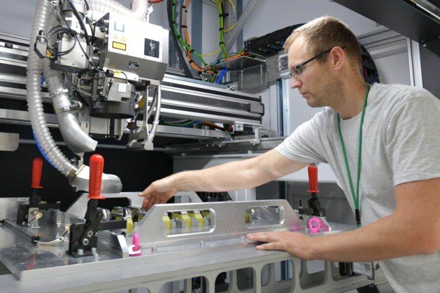 Produktionsleiter Sven Böhme richtet bei der Firma JT Energy Systems im Gewerbegebiet Ost in Freiberg den Laserschweißer für die Produktion Lithium-Ionen-Zellpacks ein.