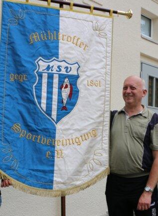 Vereinsvorsitzender Karl-Heinz Lindner zeigt die neue Vereinsfahne, die der Mühltroffer Sportverein vor fünf Jahren einweihte.