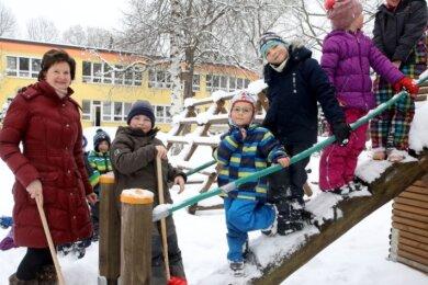Erzieherin Konstanze Drechsel mit Mädchen und Jungen, die bei Schnee gern ins Freie rasugehen.
