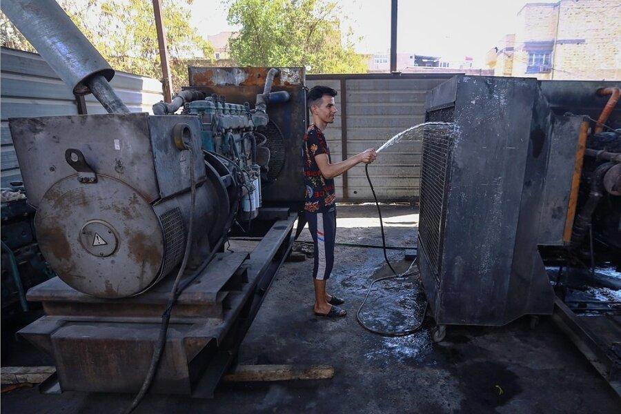 Derzeit Alltag im Irak: Ali Kazem, Besitzer eines lokalen Elektrizitätswerks, das Strom an die Haushalte liefert, kühlt seine Geräte während der anhaltenden Hitzewelle mit Wasser.