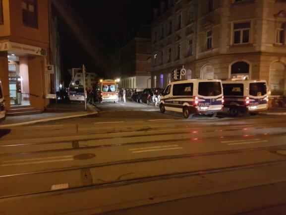 Während ein Verletzter in einem Rettungswagen versorgt wird, nehmen Polizisten die Personalien von möglichen Beteiligten und Zeugen auf.