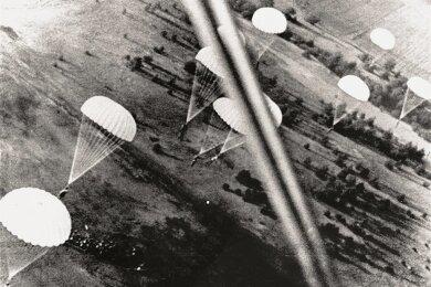 """Deutsche Fallschirmjäger beim """"Sprung in die Festung Holland"""" im Mai 1940."""
