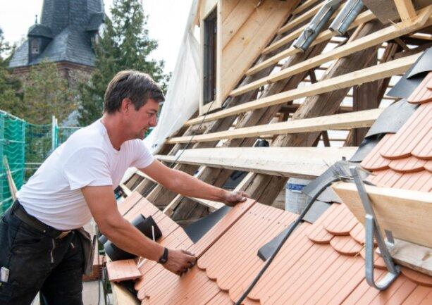 Das Pfarrhaus neben der Kirche in Schwarzbach erhält derzeit ein neues Dach. Im Foto verlegt Dachdecker Udo Hinkelmann von der Firma Lipfert Bedachungen Bad Lausick Biberschwanzziegel.