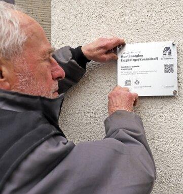 Reiner Hoffmann bringt die Unesco-Plakette der Montanregion Erzgebirge am Drei-Brüder-Schacht an.