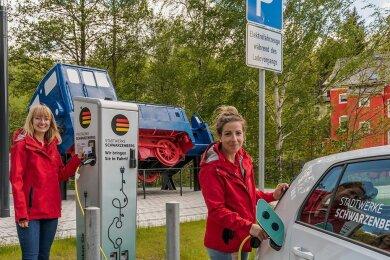 Franziska Paulus und Adrienne Sargatzke von den Stadtwerken Schwarzenberg testen die Ladesäule am Hammerweg.