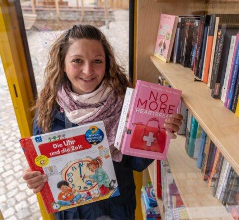Franziska Gündel in der ehemaligen Telefonzelle, die auf dem neuen Dorfplatz in Wildenau als Platz zum Büchertausch aufgestellt wurde. Die junge Mutter hatte die Idee dazu und will sich auch künftig um den Treffpunkt für Leseratten kümmern.Foto: David Rötzschke