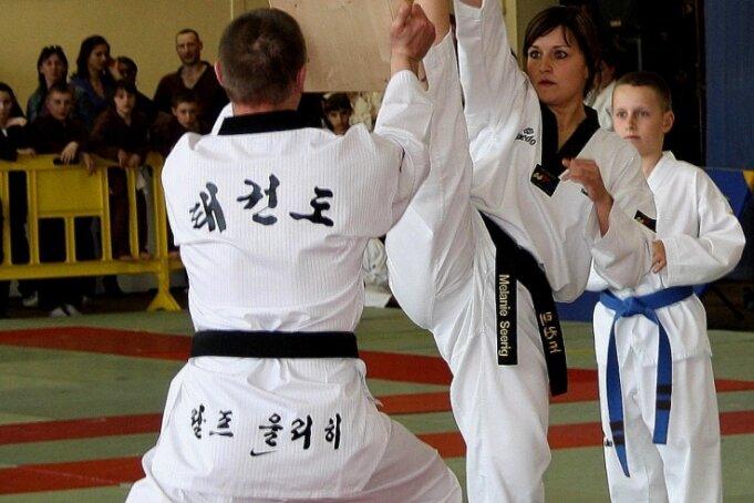 Seit fast 30 Jahren trainiert Ralf Uhlich (vorn) die Freiberger Taekwondosportler, hier Melanie Seerig. Dabei demonstrierten sie ihre Kampfkünste sogar bei einer Sportgala in der französischen Partnerstadt Gentilly.