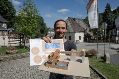 Sebastian Guthke mit dem Bastelbogen, mit dem die Kinder ihr eigenes kleines Hammerwerk bauen können.