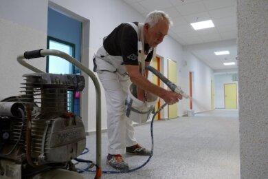 Das Schulhaus wird aufgemöbelt: In der Grundschule Am Zschopenberg bläst Jürgen Sehm mit einem Kompressor Multicolor-Floc-Chips an die Wand und verleiht dem Korridor so ein frisches Aussehen.