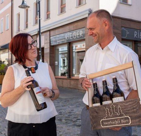 """Steffen Fohlert (rechts) wird sein """"Awerbacher Bier"""" künftig hinterm Haushaltwarengeschäft Rieger brauen und im Geschäft von Christine Rieger (links) anbieten - auch in einer neuen """"Männerhandtasche""""."""