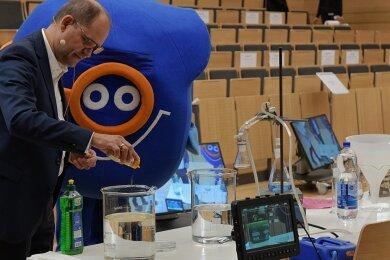 Junioruni im Freiberger Audimax und von dort ins Internet: Professor Traugott Scheytt erklärt mithilfe verschiedener Apparaturen den Wasserkreislauf, Maskottchen TU-Lino weicht ihm nicht von der Seite.