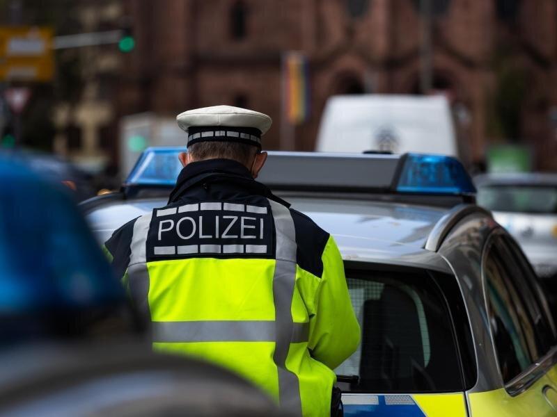 Ein Polizeibeamter steht zwischen zwei Einsatzfahrzeugen der Polizei.