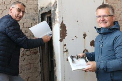 Flöhas Oberbürgermeister Volker Holuscha (links) und Bauamtsleiter Andre Stefan haben in einem alten Tresor im ehemaligen Verwaltungsgebäude der Alten Baumwolle eigenartige Dinge gefunden.