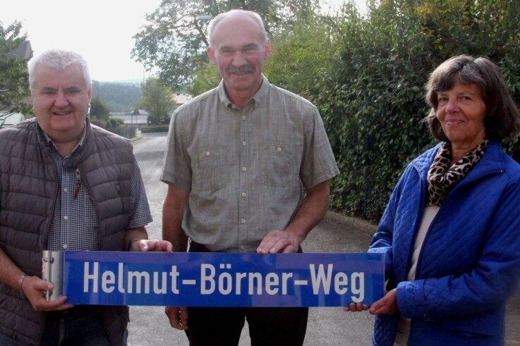 Das Schild Helmut-Börner-Weg halten Börners Tochter Katharina (rechts) sowie Lutz Kätzel vom Ortschaftsrat und Andreas Oberlein (links) in den Händen.