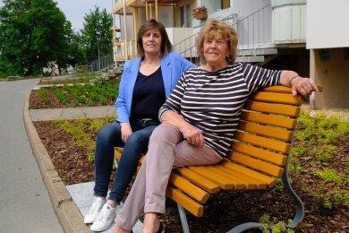 Carmen Brückner von der Woba und Mieterin Regina Fehlhauer auf einer der neuen Bänke an der Andreas-Schubert-Straße.