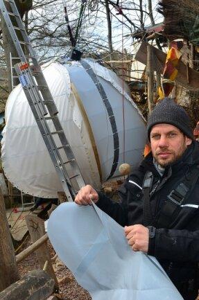 """Stev Bringmann zeigt die Folie für das kugelförmige Baumhaus in Leichtbauweise (hier im Hintergrund), dass derzeit im """"Kriebelland"""" an der Talsperre Kriebstein entsteht."""
