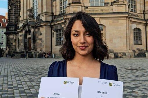 Stolz zeigt Hala Sheikh Ayoub ihr Abizeugnis, das sie von Frank Triebsch, Schulleiter am Freiberger Kolleg, bekommen hat.