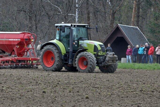 Etliche Schaulustige beobachten die Zugmaschine beim Aussäen der Saatgutmischungen für eine große Blühwiese. Zwei verschiedene Mischungen sollen sich später auch optisch auf der Fläche unterscheiden lassen.