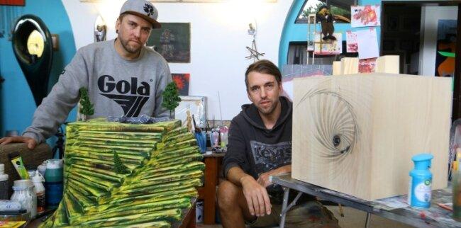 Das Künstlerduo Robby (links) und sein Bruder Marcel Oertel gestalten im Rahmen einer Kunstaktion zwei große Holzwürfel.