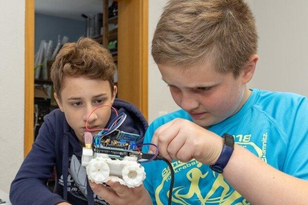 Junge Tüftler unter sich: Mika aus Burkhardtsdorf (links) und Tim aus Annaberg-Buchholz mit ihrem Smars-Roboter.