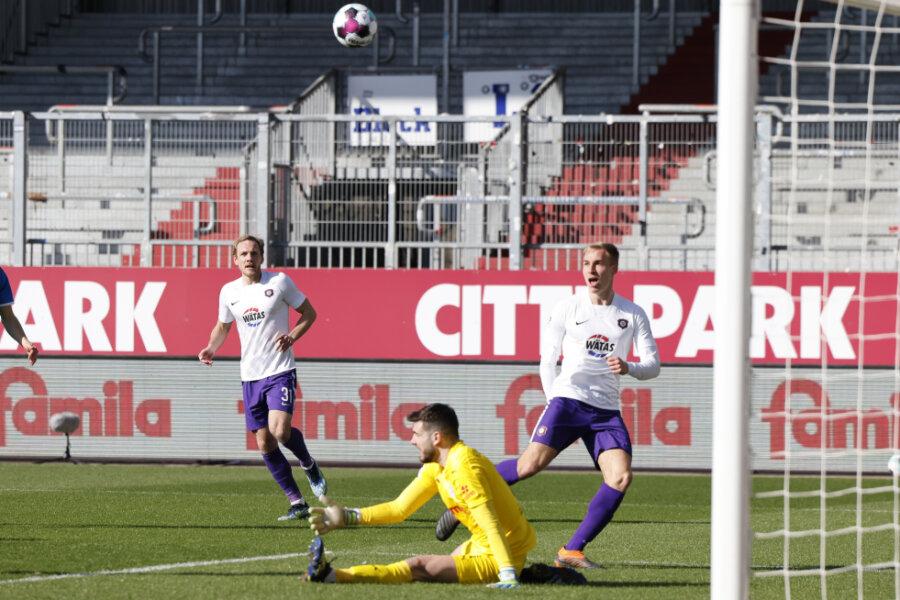 Kiels Torwart Ioannis Gelios (M) pariert einen Ball von Aues Florian Krüger (r).
