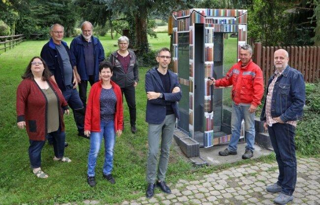 Spender Björn Grämer, Geschäftsführer bei der Kemas-Gesellschaft (Dritter von rechts) und Michael Oehler (rechts) vom Lobsdorfer Heimatverein an der zur Bücherzelle umgebauten Telefonzelle.