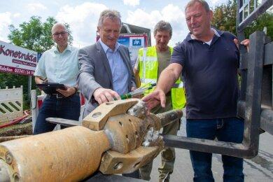 Projektleiter Frank Hoffmann und Geschäftsführer Peter Kober (Stadtwerke), Michael Pechmann und Jörg Schmidt von der Firma Schmidt Bau GmbH (von links): Solche Bohrköpfe fressen sich quasi überall durch.