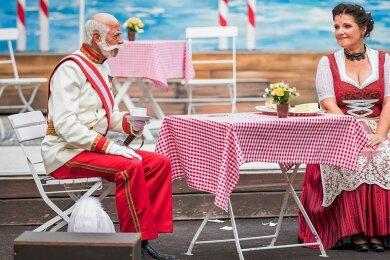 """Sogar der Kaiser - in der aktuellen Inszenierung des Eduard-von-Winterstein-Theaters auf der Freilichtbühne an den Greifensteinen gespielt von Leander de Marel - steigt """"Im weißen Rössl"""" am Wolfgangsee ab und lässt sich von Wirtin Josepha Vogelhuber - gespielt von Bettina Grothkopf - bewirten."""