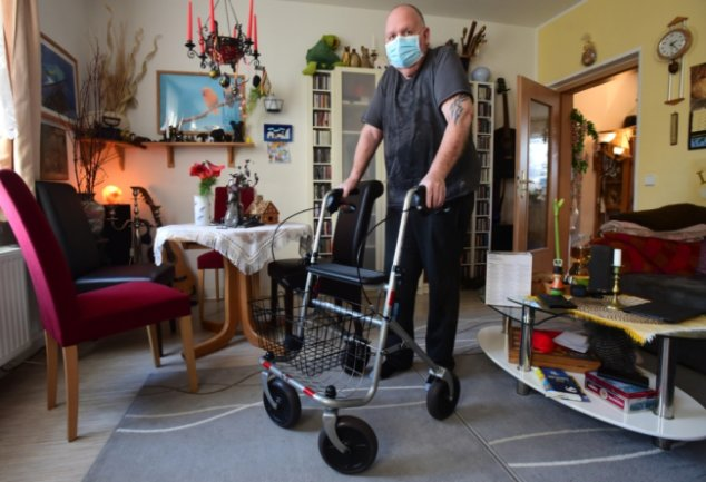 Tom Haus in seiner Wohnung in Chemnitz. Nach einer Coronaerkrankung und mehreren Tagen im Koma kann er derzeit nur mit Rollator laufen.