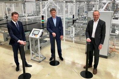 Ministerpräsident Michael Kretschmer (l.), Geschäftsführer Gunter Erfurt (Mitte) und Energieminister Wolfram Günther haben am Mittwoch symbolisch die Solarindustrie in Freiberg wieder in Gang gesetzt.